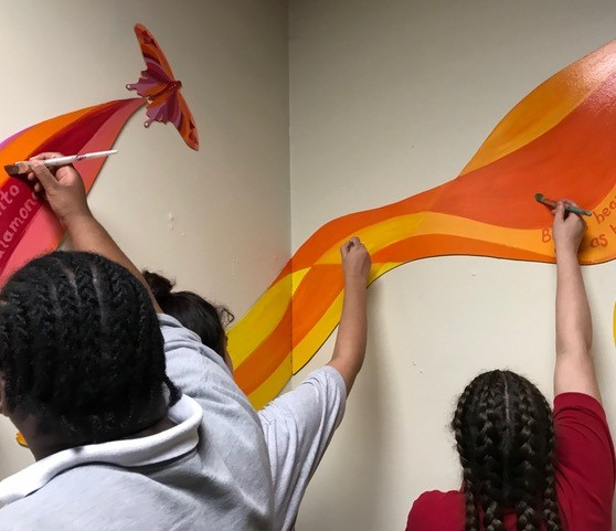 Young women painting the mural